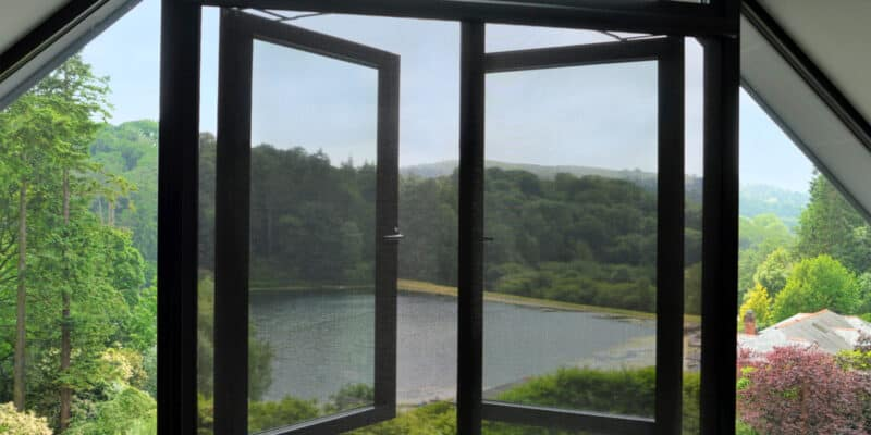 close up of window fly screens over lake and valley